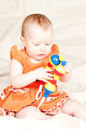 Little baby girl playing with rattle Stock Photo - 4322314