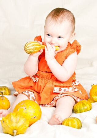 Little baby girl playing with calabash pumpkin photo