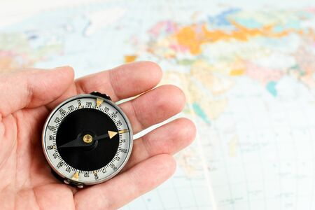 Hand holding compass with map of the world in background Stock Photo - 4399530