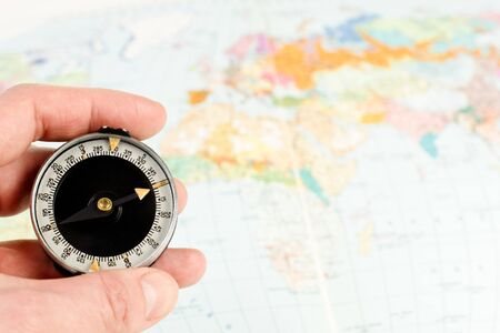 road position: Hand holding compass with map of the world in background Stock Photo