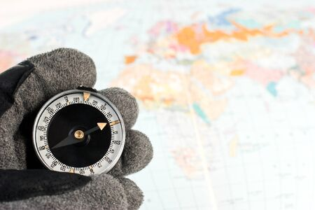 Hand in hiking glove holding compass with map of the world in background Stock Photo - 4399531