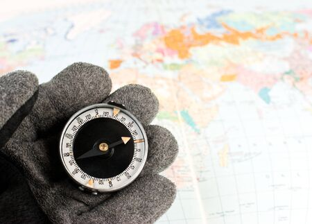 Hand in hiking glove holding compass with map of the world in background photo