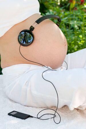 Headphones on a pregnant woman's belly Stock Photo - 4428759