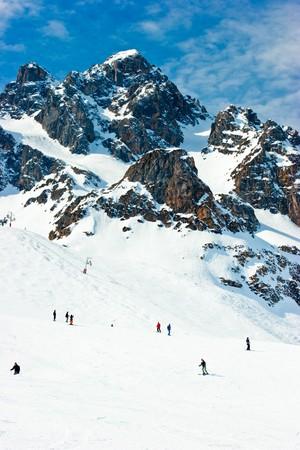 Skiers on a piste at Alpine ski resort photo