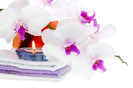 Spa set with white orchid, towels, shell and burning candle on white background photo