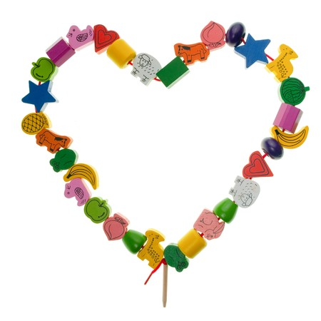 Colorful wooden toy beads in the shape of heart on white background photo