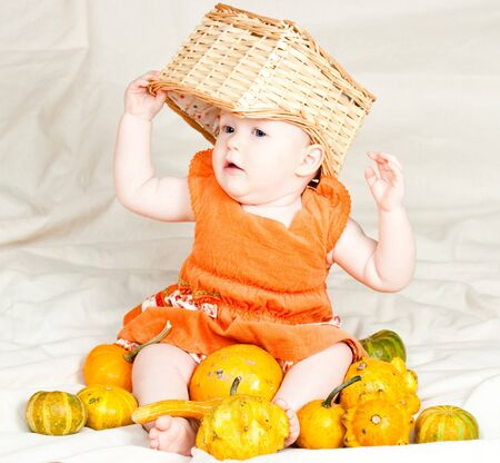 Little baby girl playing with pumpkins and box photo