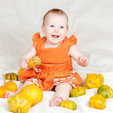 Little baby girl playing with pumpkins photo