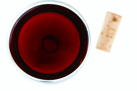Glass of red wine and cork, focus on top of glass