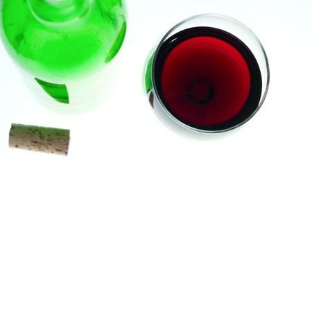 Glass of red wine, bottle and cork, focus on top of glass photo