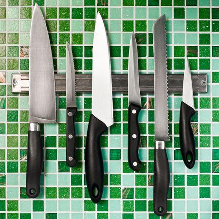 Kitchen knives on green mosaic wall photo
