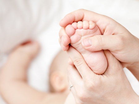 Mother massaging her childs foot, shallow focus photo