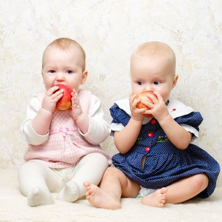 Two little baby girls eating apples Stock Photo
