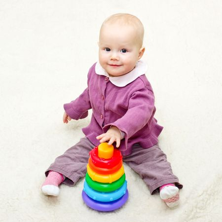 Baby girl playing with color pyramid photo