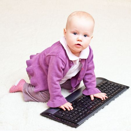 Baby girl playing with computer keyboard photo