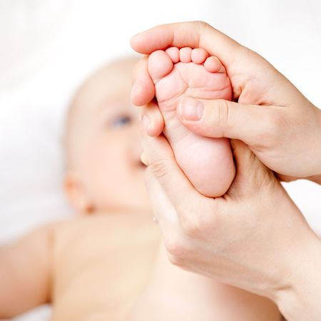 Mother massaging her child's foot, shallow focus Stock Photo - 4740886