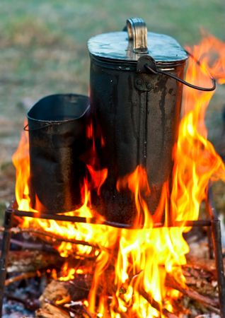 Two camping kettles over burning campfire photo