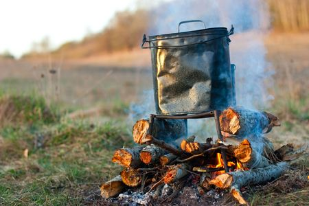 soup kettle: Camping kettle over burning  campfire in the morning light Stock Photo