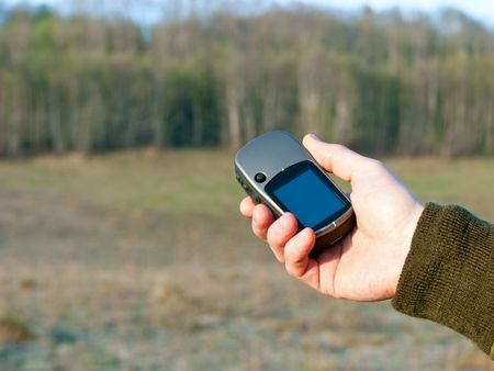 Hand holding GPS navigator with spring field in background Stock Photo - 4942823