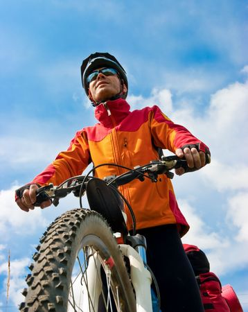 Portrait of adult cyclist on mountain bike against blue sky Stock Photo