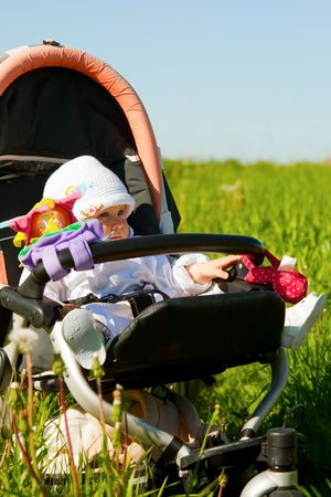 Little baby girl sitting in stroller on nature photo