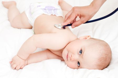 Childrens doctor exams infant with stethoscope