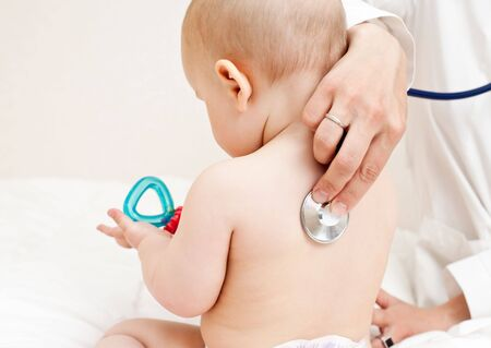 Childrens doctor exams infant with stethoscope photo