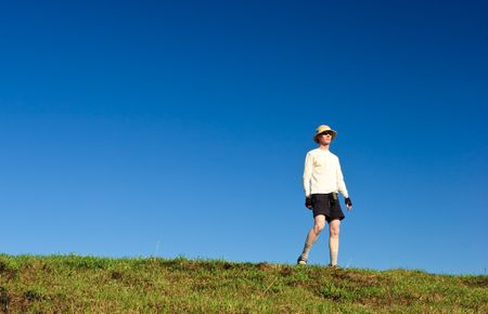 Hiker on a hill against clear blue sky Stock Photo - 5012169