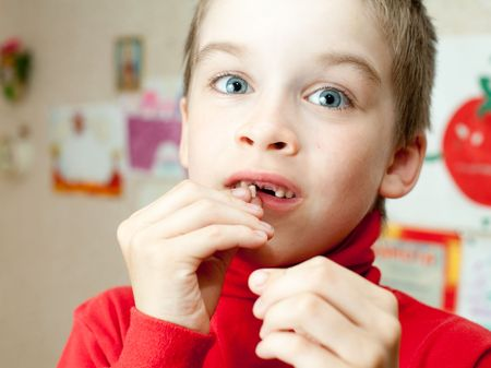 Boy holding lost deciduous teeth against his drawing on the wall Stock Photo - 5012175
