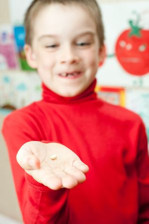 Boy with deciduous tooth in his hand, shallow focus photo