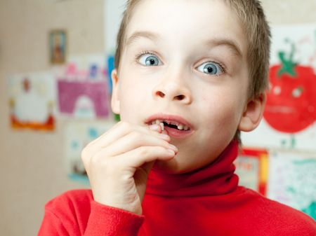 Boy holding lost deciduous teeth against his drawing on the wall photo