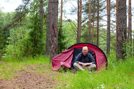 Cheerful tourist sitting in red tent in a forest Stock Photo - 5104513