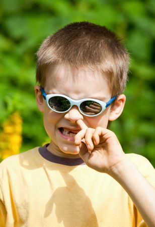 Portrait of a young boy wearing sunglasses picking his nose photo