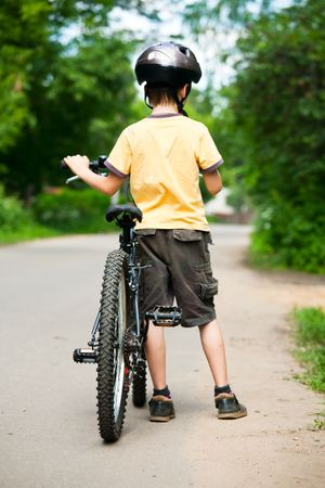 Young boy standing with bicycle, shallow dof photo