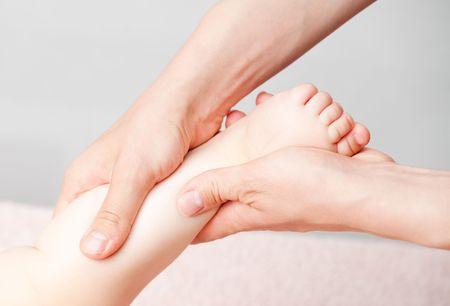masseuse: Masseuse massaging little baby girls foot, shallow focus