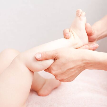 Masseuse massaging little baby girls foot, shallow focus photo