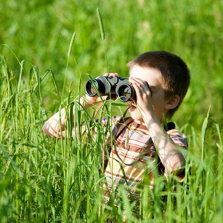 Jeune garçon à la recherche dans un champ avec des jumelles Banque d'images