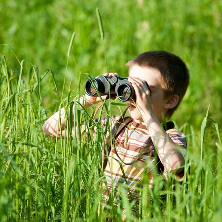Young boy in a field looking through binoculars Stock Photo