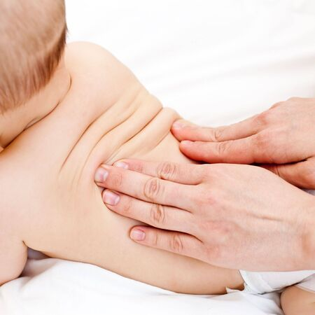 Masseuse massaging little baby girl, shallow focus photo