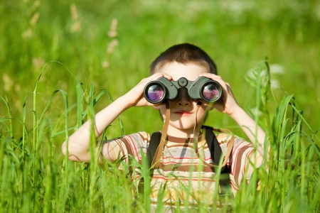 Young boy in a field looking through binoculars Foto de archivo