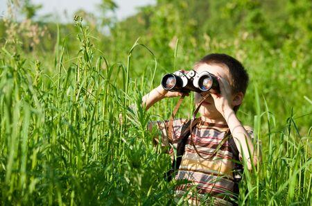 schoolkid search: Ni�o en un campo mirando a trav�s de los binoculares