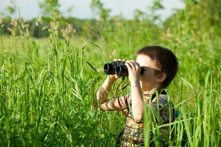 ni�os pensando: Ni�o en un campo mirando a trav�s de los binoculares