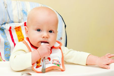 highchair: Little baby girl sitting in highchair with spoon