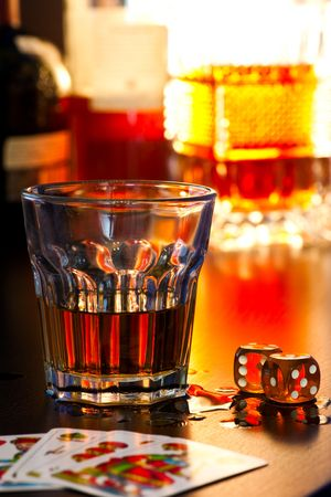bad fortune: Glass of whiskey with dice and playing cards, shallow DOF Stock Photo