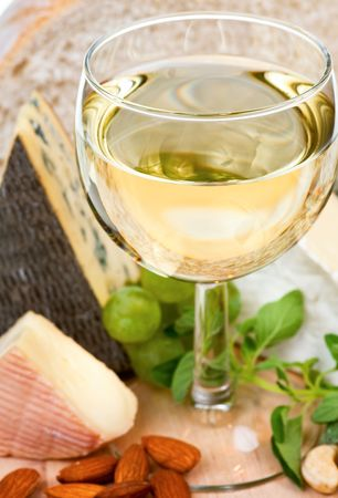 Glass of white wine with cheese at background, shallow DOF photo