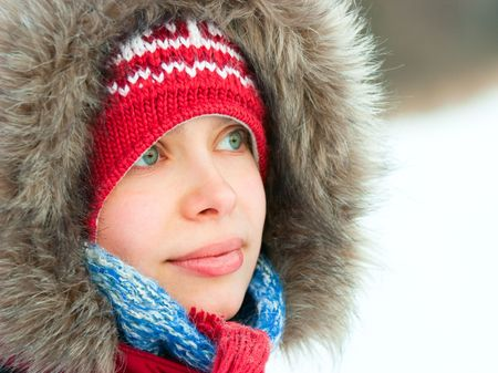 Young woman wearing furry hood and winter hat photo