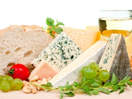 Various types of cheese and garnishes on wooden plate photo