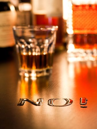 no alcohol: The word No written with spoiled whiskey on a table, shallow DOF