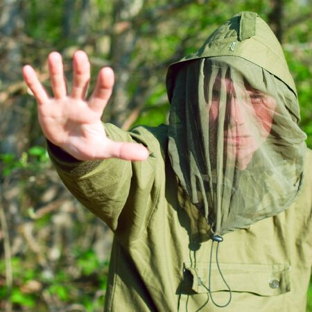 Man wearing encephalitis protective clothing hold up his hand outdoors, shallow DOF Stock Photo - 5203864