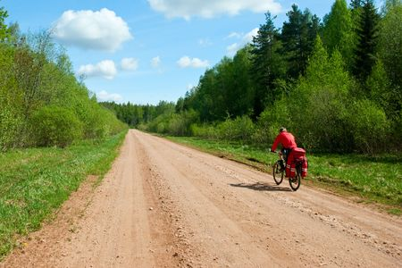 Traveling cyclist on dirt road photo